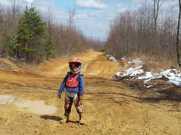 Little boy in riding gear on dirt road