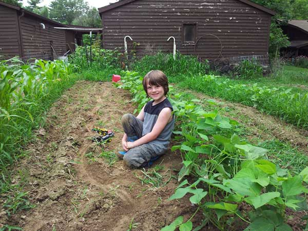 My son Asher in the half weeded garden