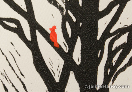 close up of red bird perched on black tree branches mono-print