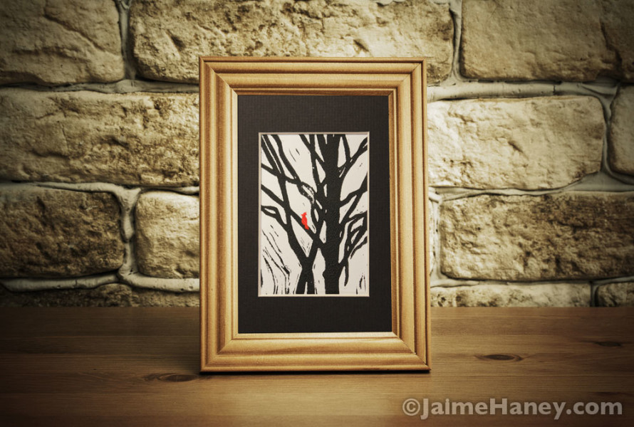 red-bird-black-tree,-blk-mat-shown-in-frame-on-desk
