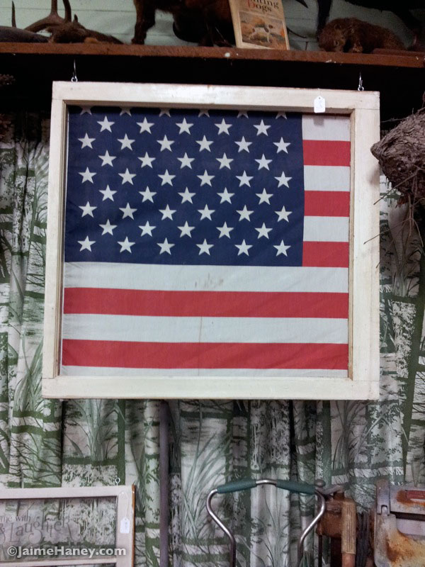 Old American flag framed in a white wooden frame