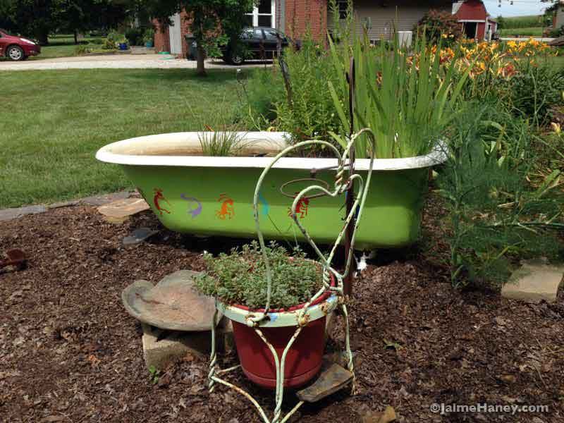 garden vignette with claw foot tub and ice cream parlor chair