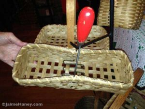 A handmade basket with a potato masher handle.