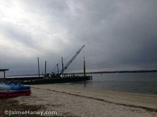 A crane pounding down a pile on the pier.